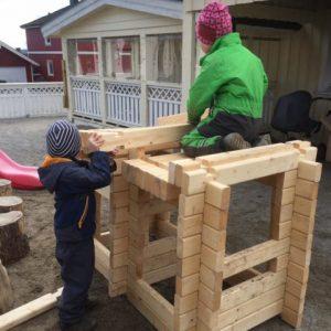 To gutter som bygger et laft hus. Foto