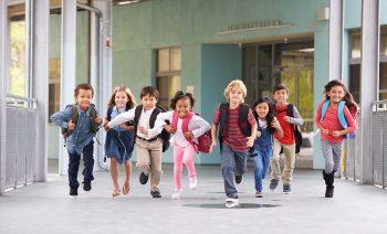 Barn som løper i en skolekorridor. Foto