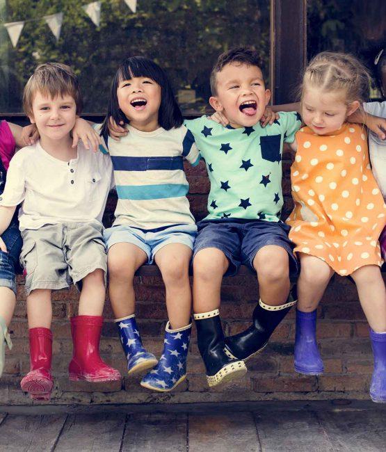 Seks barn som sitter sammen på en krakk. Foto